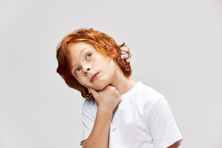 A pensive red-haired boy